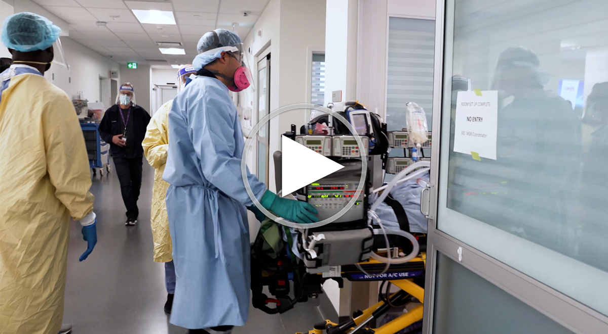Health care workers pushing a hospital bed into a room